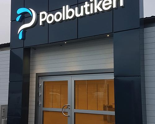 Poolbutiken - Portal med belyst skylt